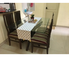 Glass top 4-seater dining table of teak wood